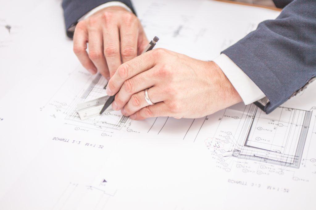 zwei Hände über einem Bauplan, ein silberner Rind ist erkennbar