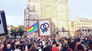 Eine große Gruppe demonstrierender Menschen mit Regenbogenflaggen und Schildern vor einer Kirche.