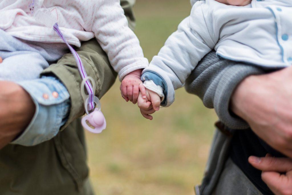 Zwei Baby halten sich an der Hand